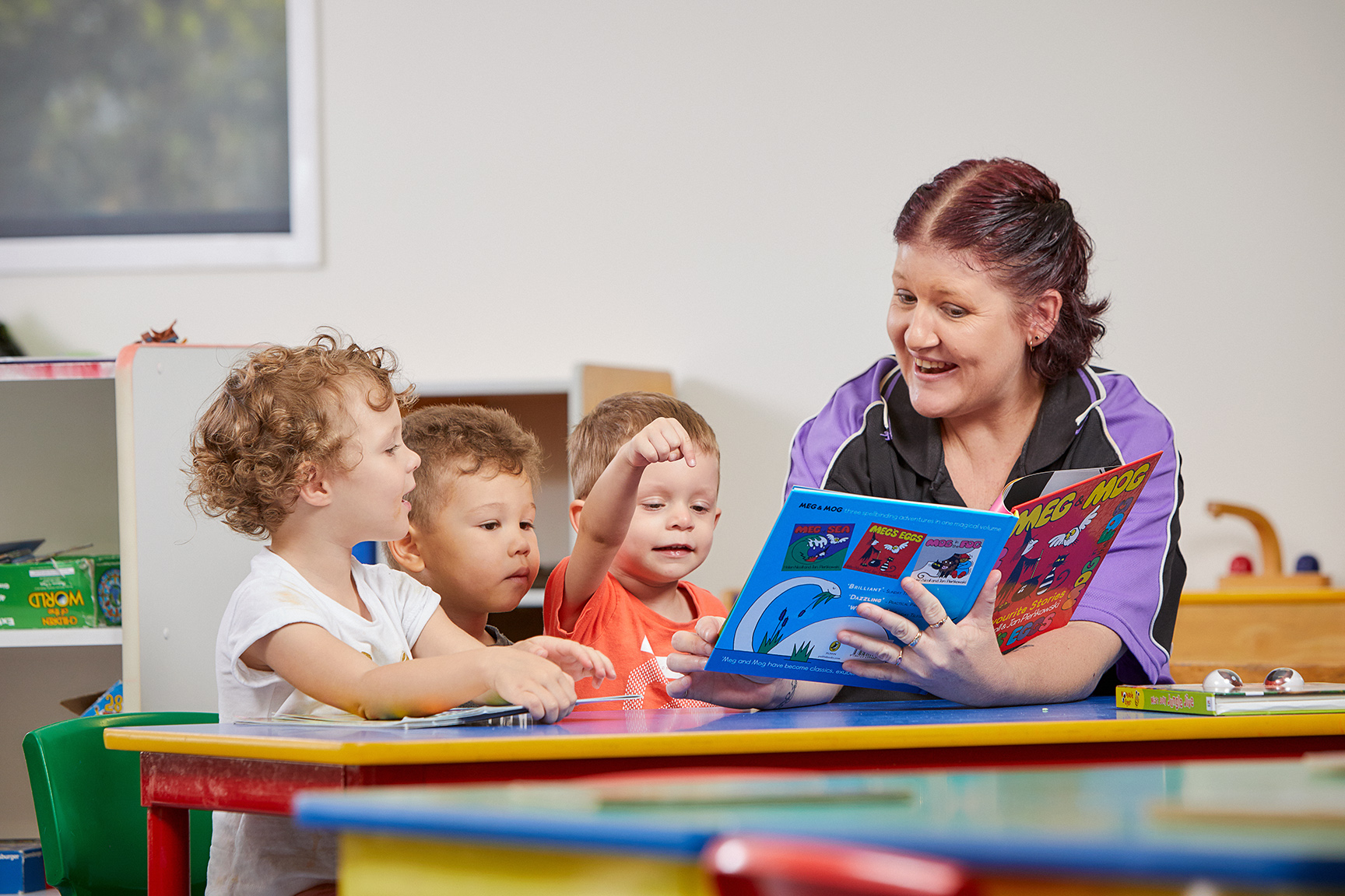 A Child care educator reading a book to 3 toddlers in a classroom
