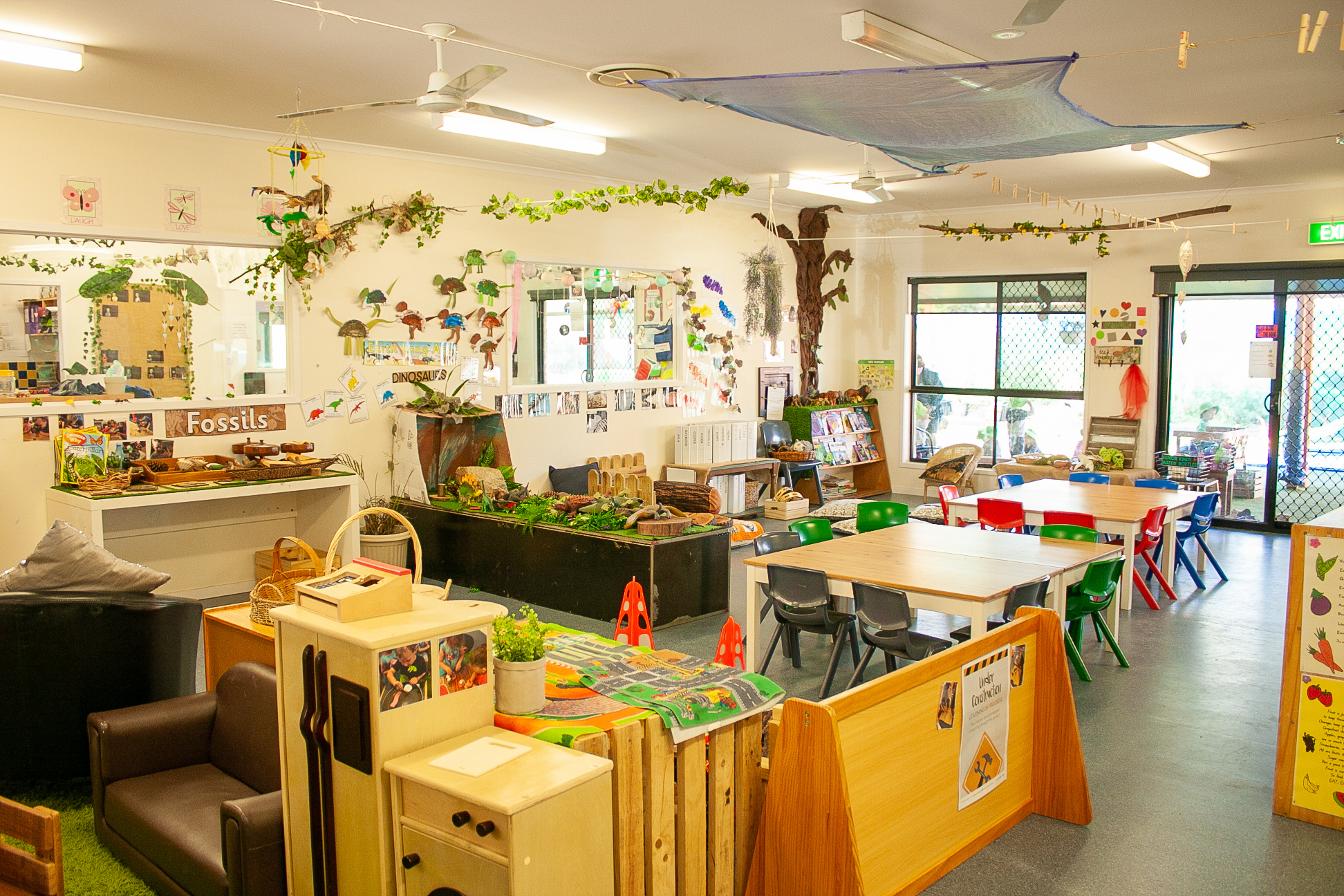 Colourful classroom with art and craft pieces hanging from ceiling